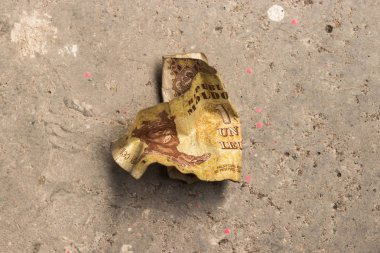 Crumpled banknote of the Republic of Moldova - LEU on the concrete floor.