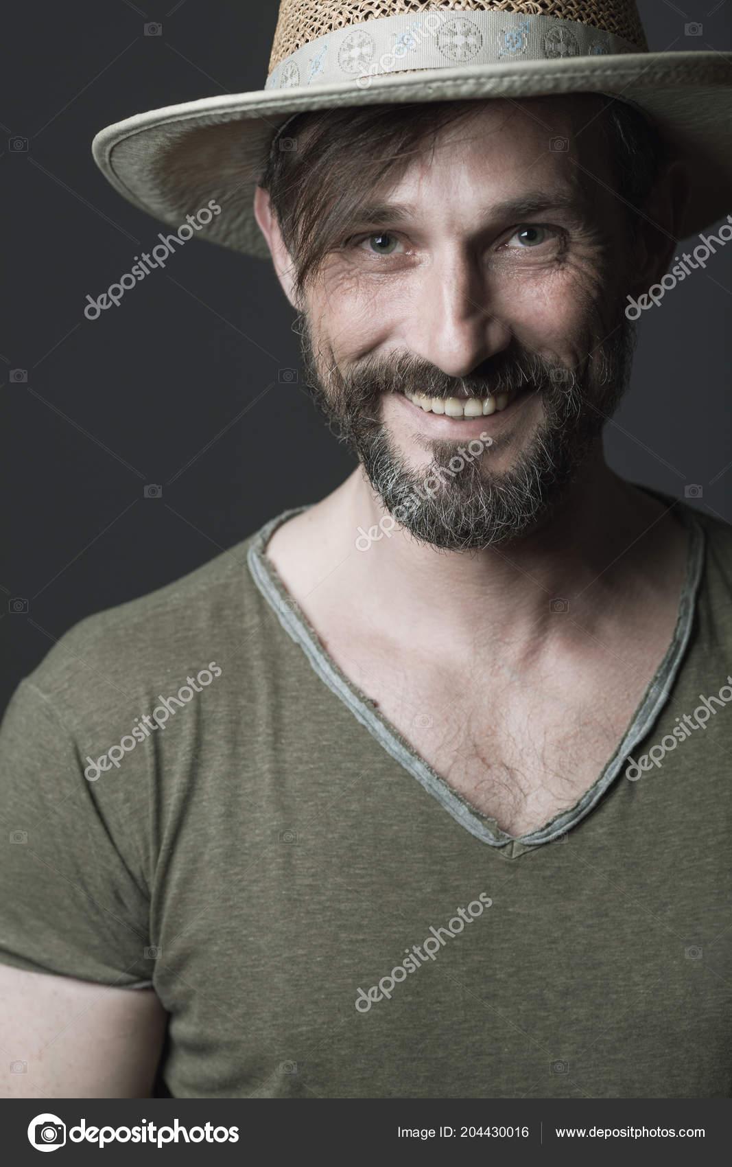 Ritratto di risata 40-anno-vecchio uomo nella condizione di cappello di  paglia sopra fondo grigio scuro. Capelli lunghi sulla fronte. Stile country  estate. 2de01a3a4644