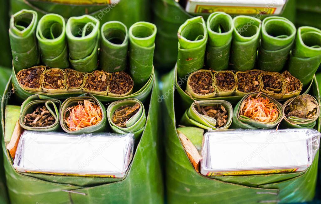 Tobacco and betel nut and betel leaf, Tobacco and betel nut and betel leaf preparing for eat on the old wood, Ripe areca-nut and green betal leaf. Part of Brahman ceremony.