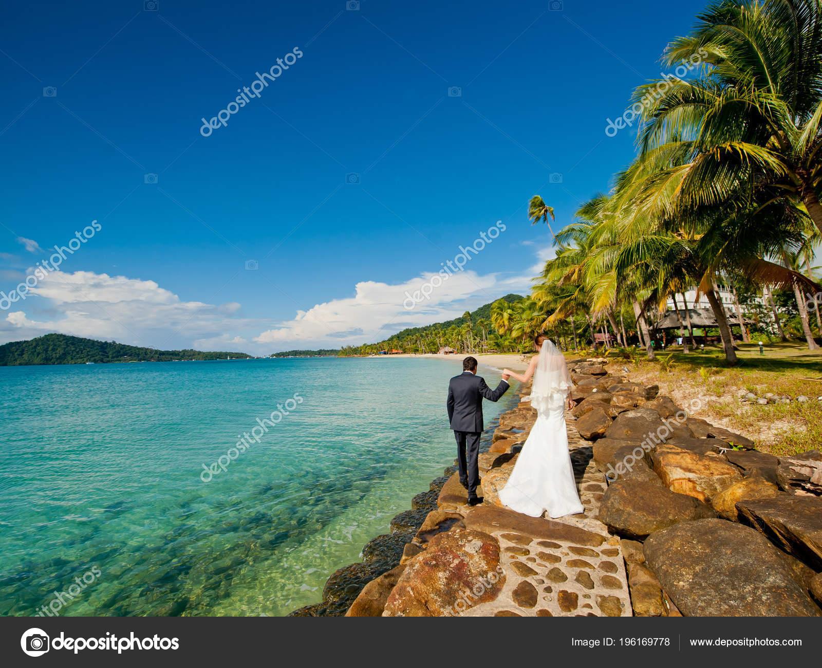 6d6d23d8aa0e4b Bride Groom Wedding Suits Holding Hands Walking Stone Pier Tropical ...