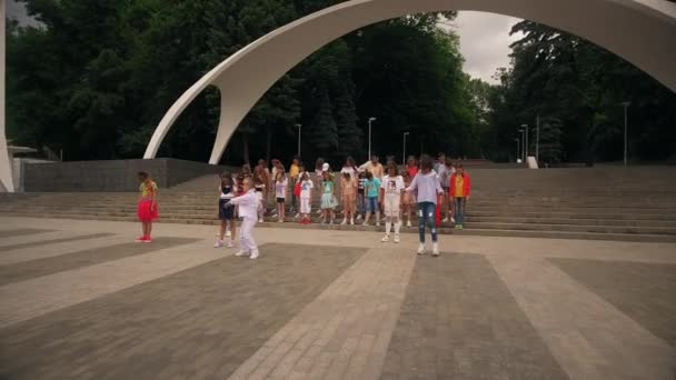 Vinnytsia Ukraine - June 07, 2019: A group of children sings and dances against the backdrop of the entrance to the park. Aerial view.