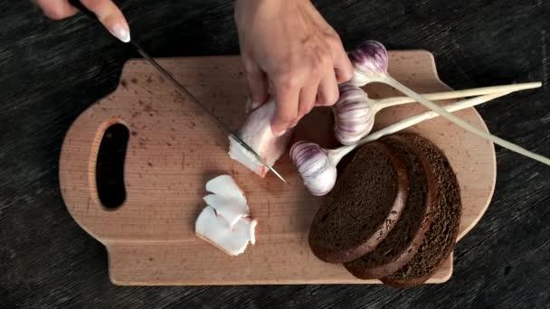 Samičí ruka řeže nožem čerstvý tuk na dřevěné desce. Černý chléb a česnek. Zpomalený pohyb.