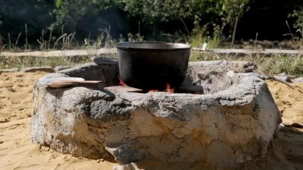 Egy nagy üstöt a máglyán. Tűzön főtt étel.