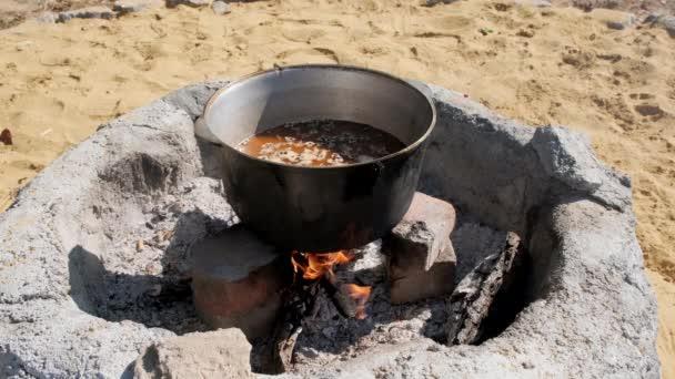 Pilótát főzni egy nagy üstben egy nyílt tűz felett. Közelkép.