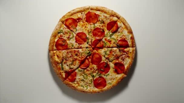 Muž bere kus velké pizzy ze dřevěné desky