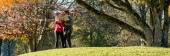 Boldog fiatal család, két gyerek időt együtt az őszi parkban a napsütéses napon.