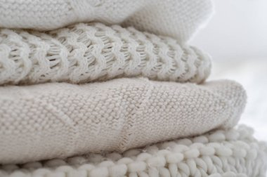 Background with warm sweaters. Pile of knitted clothes in warm shades, space for text, Autumn winter concept. Copy Space.