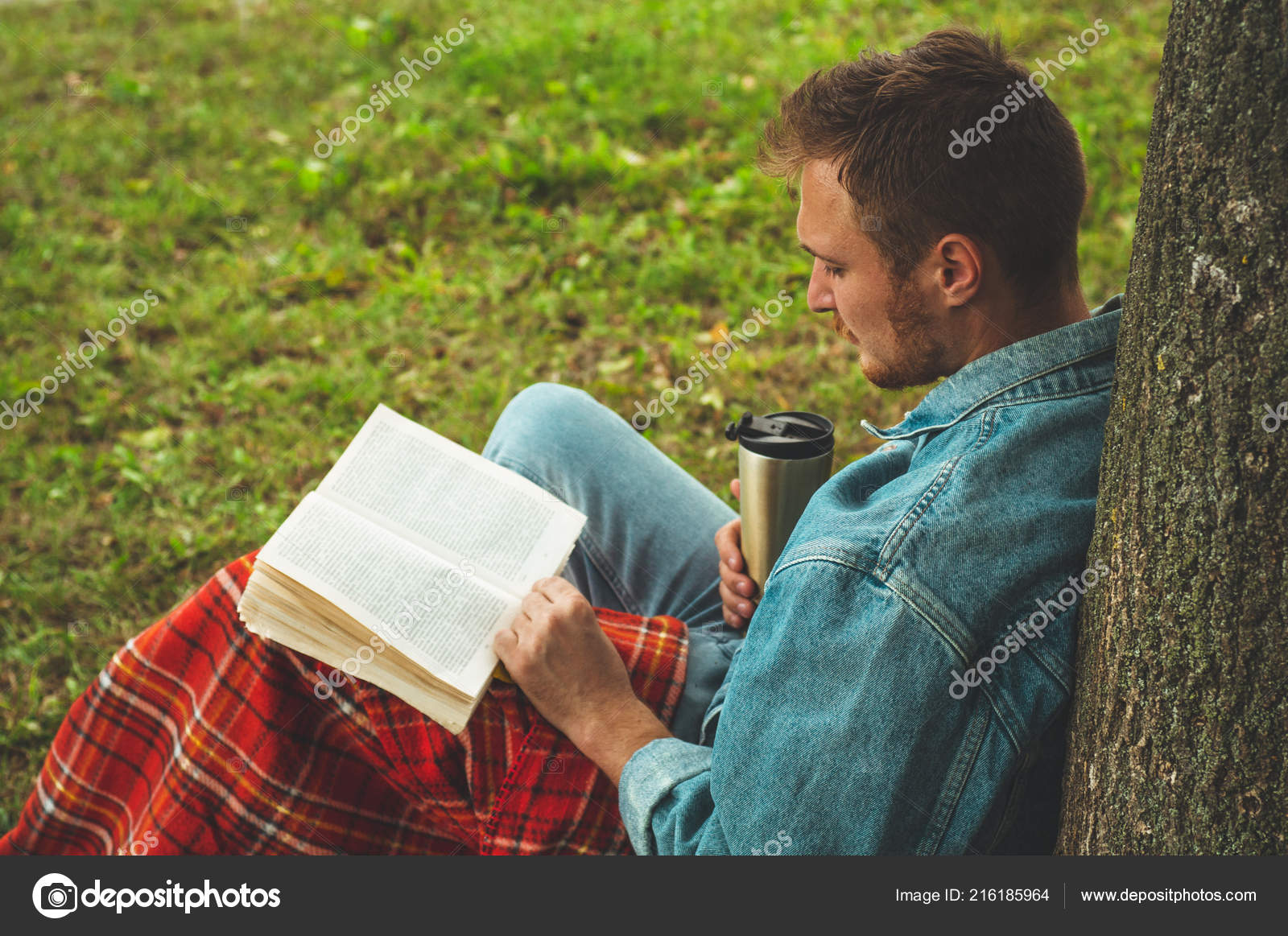 7ec009c1 Smiling Young Man reading book outdoor with a warm red plaid and a cup of  tea on background Autumn vacations and Lifestyle concept.