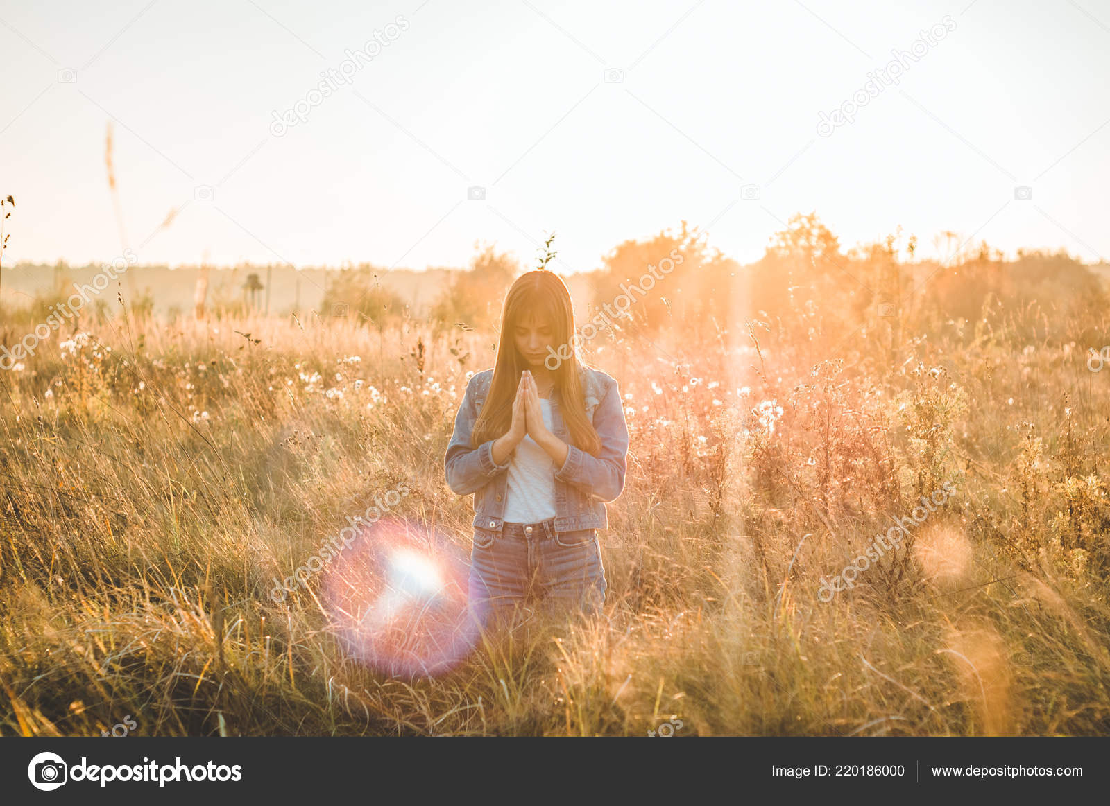 Girl closed her eyes, praying outdoors, Hands folded in