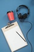 Composizione appartamento laica con cuffie, microfono e caffè su una priorità bassa blu. Concetto di podcast o webinar.