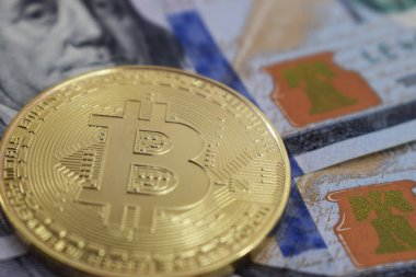 coin bitcoin against a background of dollars close up