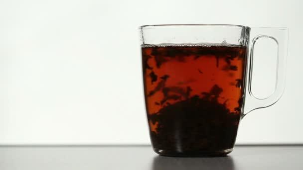 Rotující čajové listy v jasné, šálek čaje