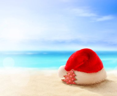 Christmas holidays concept. Santa claus hat on summer sand beach