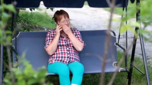 středního věku-žena sedí na zahradní houpačce a mluví o telefonu