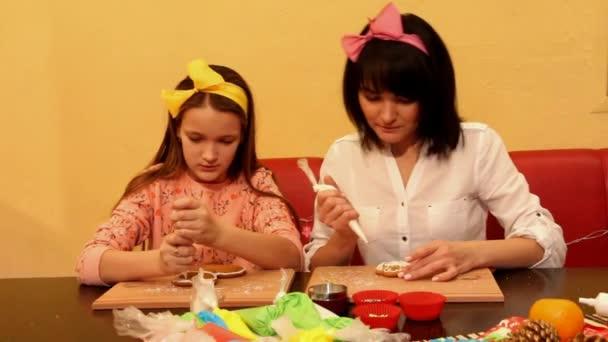 Máma a dcera malovat perníčky a mluvit u stolu