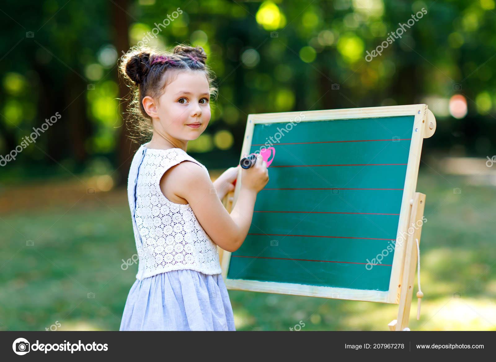 Heureux enfant fillette debout de craie grand bureau préscolaire