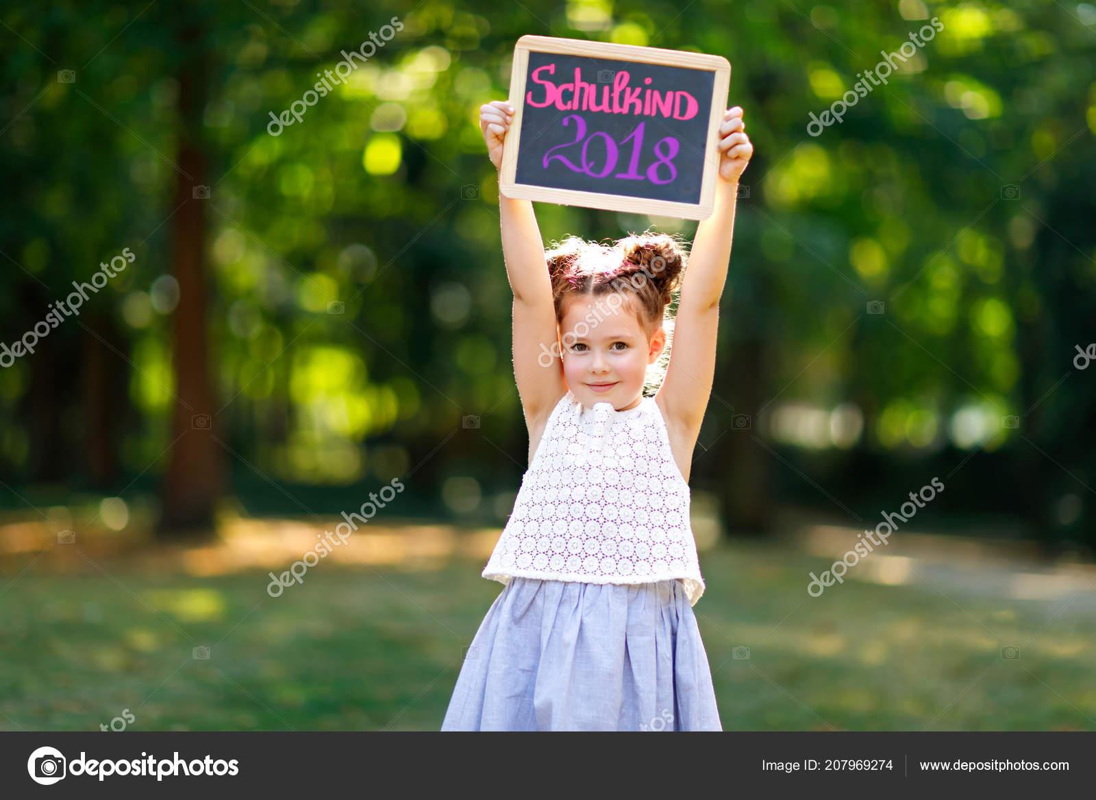 Heureux enfant fillette tenant le bureau vide de craie en mains