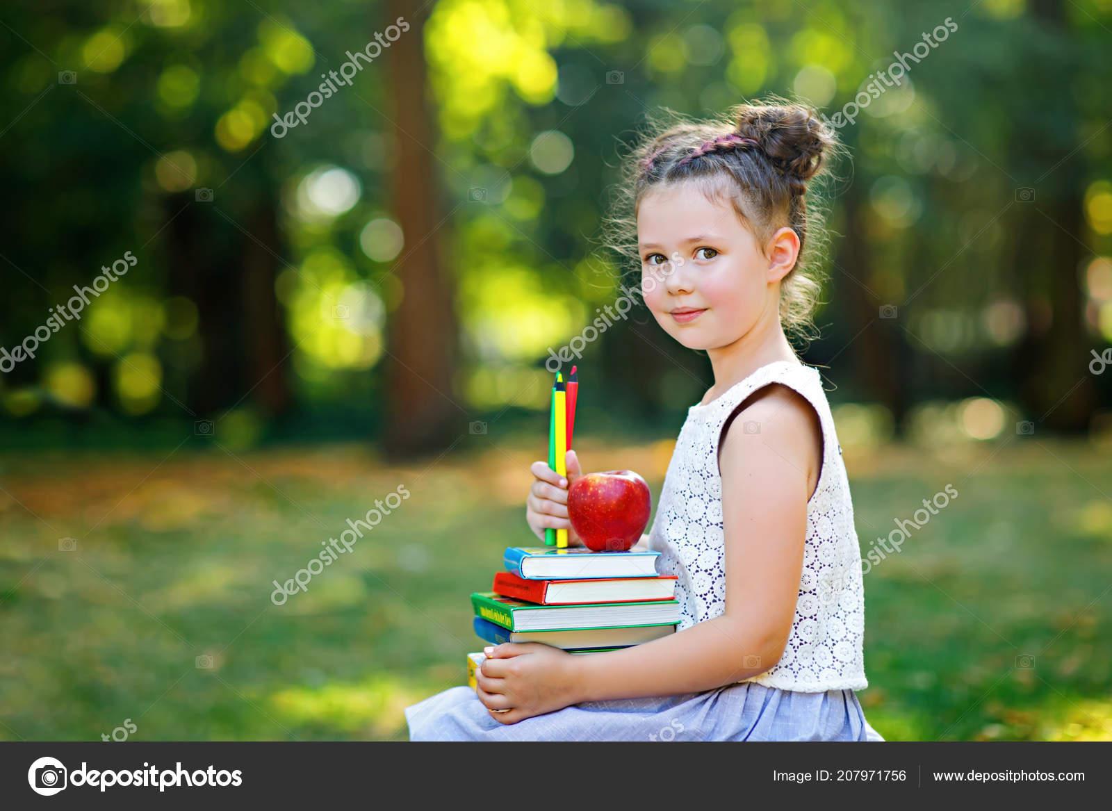 Feliz adorable niño niña lectura libro y celebración diversos libros  coloridos, manzanas y lápices primer día a la escuela ...