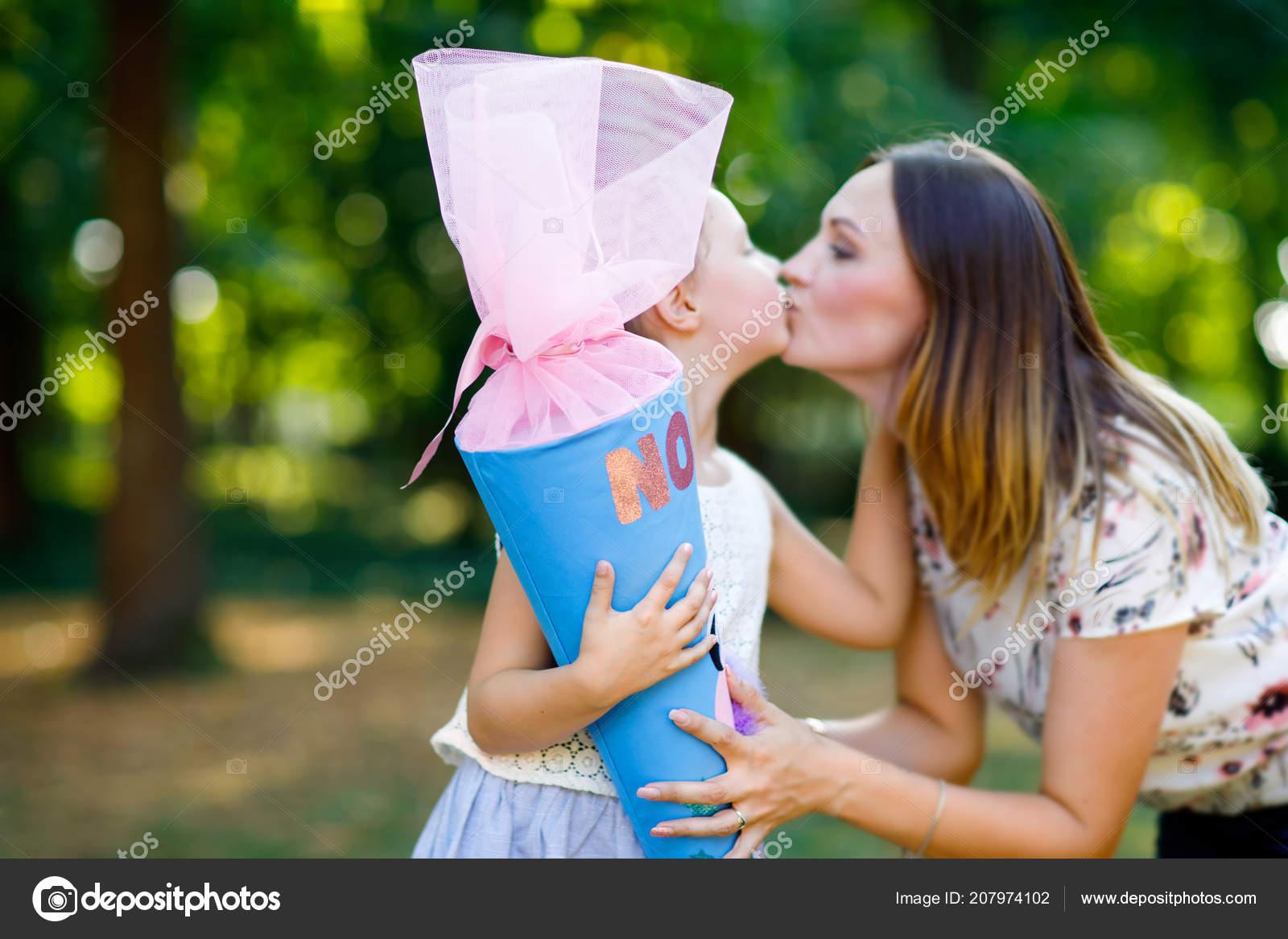 Feliz niño niña y madre con cono de regalo gran escuela tradicional en  Alemania. potache en primer día de clase primaria. Regresar al concepto de  escuela.