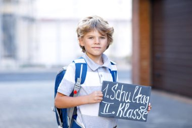Happy little kid boy with backpack or satchel. Schoolkid on the way to school. Healthy adorable child outdoors On desk