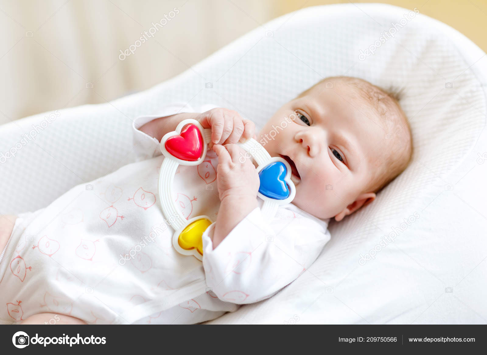 Cute Healthy Newborn Baby Playing With Colorful Rattle Toy In White Bed At Home New Born