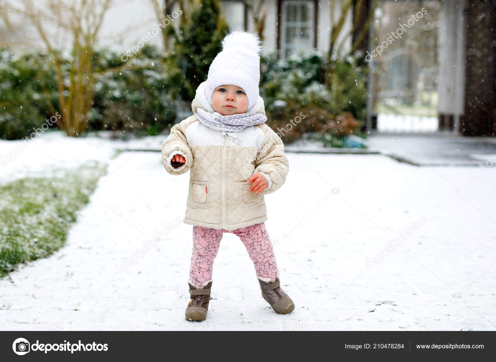 07454301b169 Adorable little baby girl making first steps outdoors in winter ...