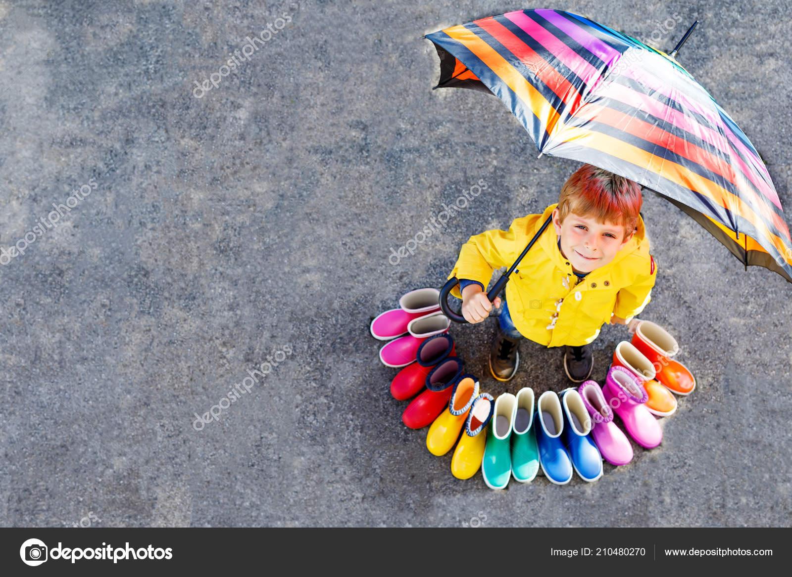 a4155d450b8 Garoto menino e grupo de galochas coloridas. Criança loira em pé sob o  guarda-chuva. Close-up de aluno e botas de borracha diferentes de alto  ângulo.