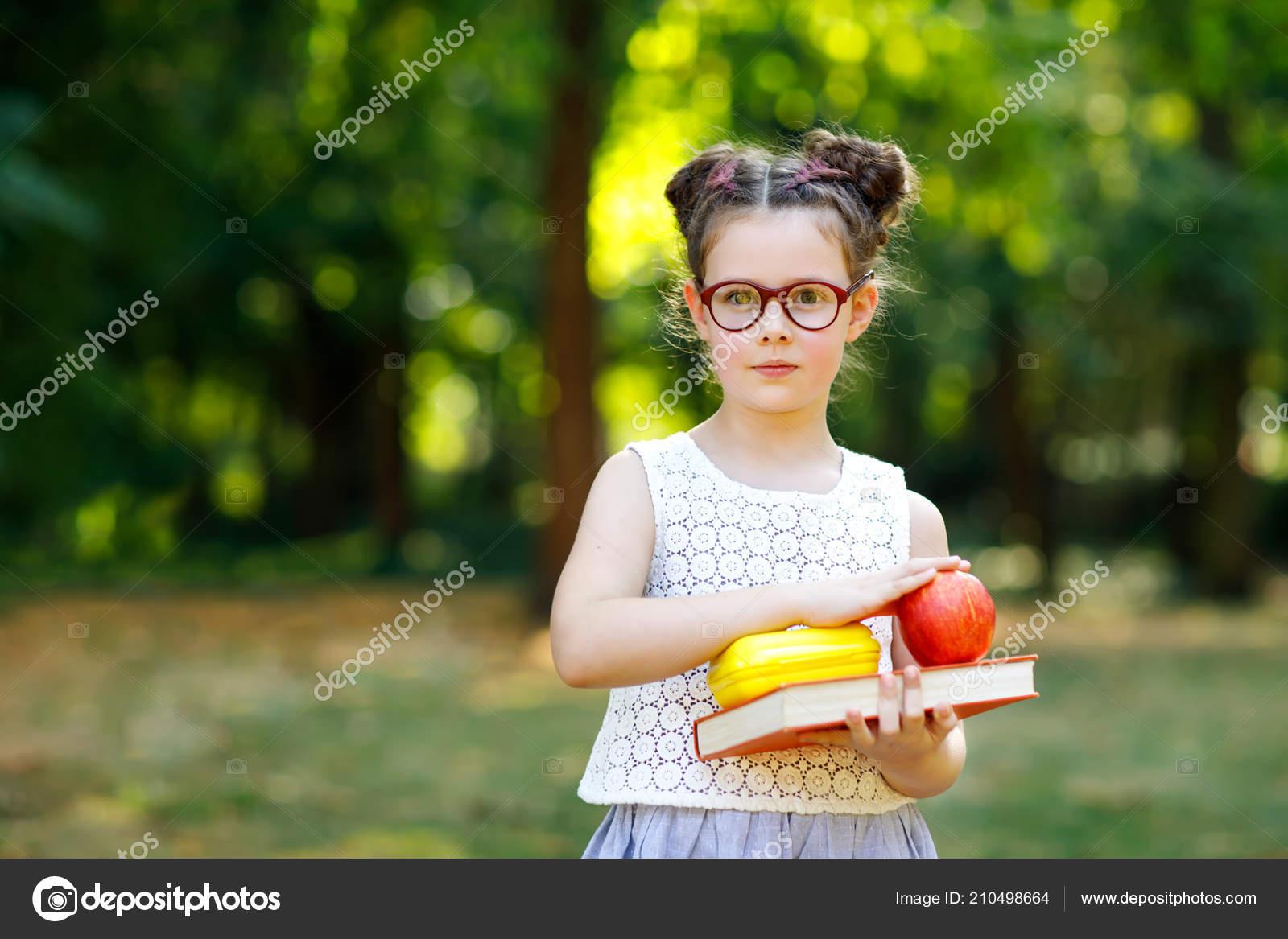 Divertida adorable niño niña con lentes, libro, manzana y mochila el primer  día a la escuela o guardería. Niño al aire libre en día asoleado caliente,  ...