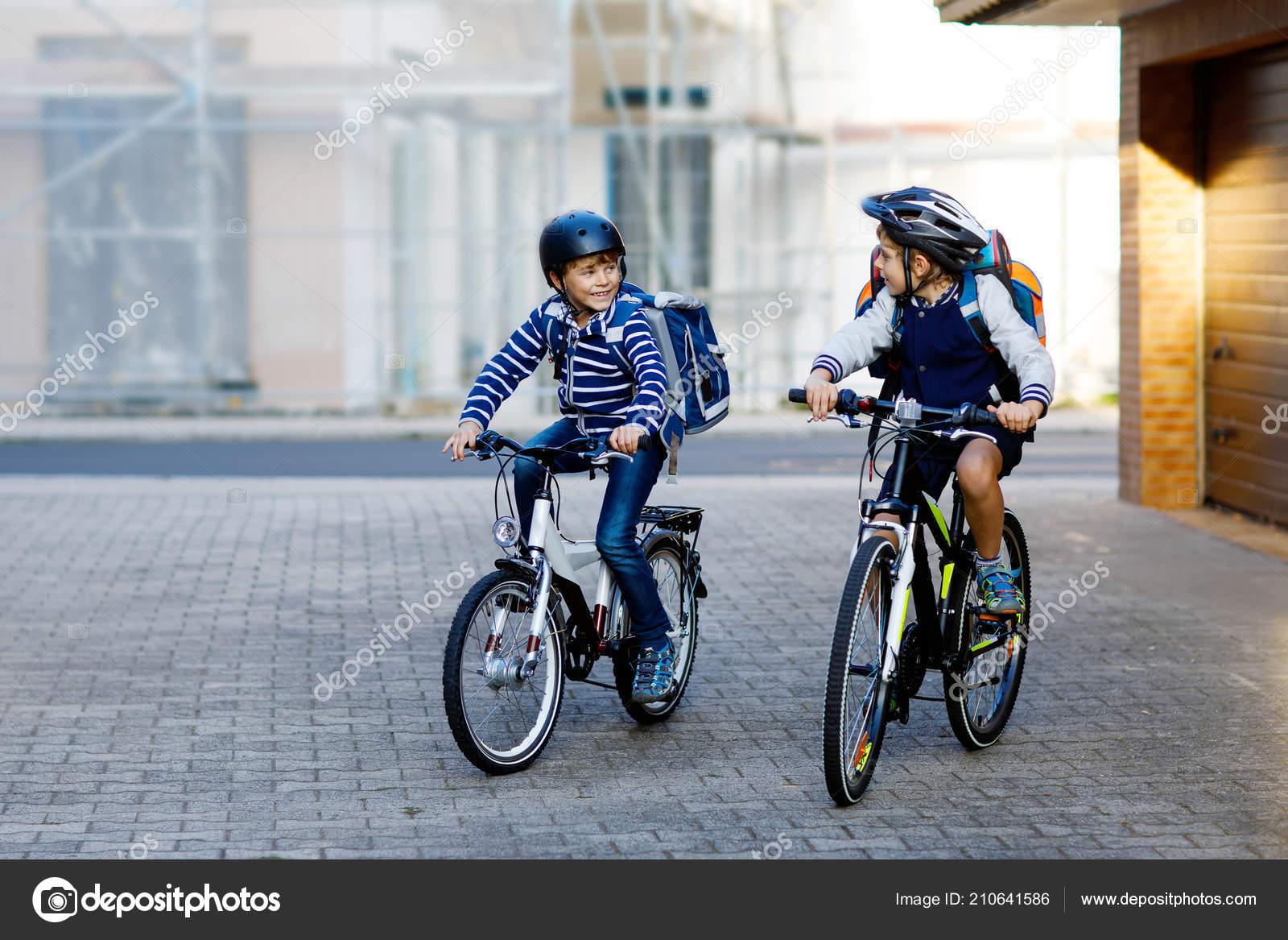 Δύο σχολείο παιδί αγόρια στο κράνος ασφαλείας ιππασία με το ποδήλατο στην  πόλη με Σακίδια. Ευτυχισμένα παιδιά με πολύχρωμα ρούχα ποδηλασίας στα  ποδήλατα στο ... c8759644a1a