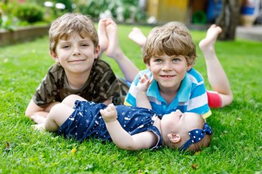 Two little happy kid boys with newborn baby girl, cute sister. Siblings on grass in summer or spring in garden. Kids bonding. Family of three children.