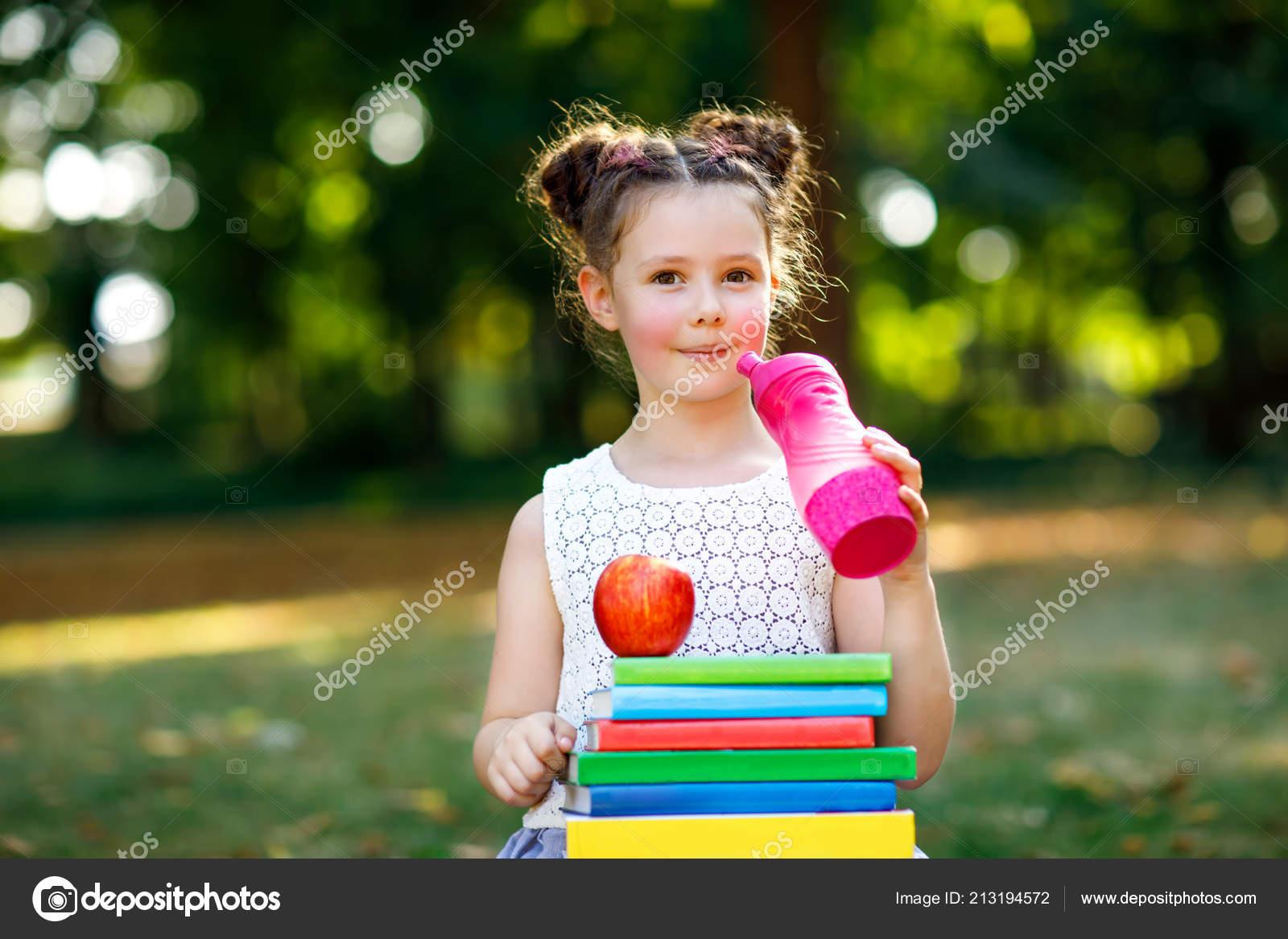Feliz adorable niño niña leyendo libro y celebración diversos libros  coloridos, manzanas y botellas de agua en el primer día a la escuela o  guardería.