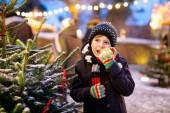Fotografie Der kleine süße Junge isst Bratwurst und trinkt auf dem Weihnachtsmarkt heißen Kinderpunsch. Glückskind auf dem traditionellen Familienmarkt in Deutschland, München. Lachender Junge in bunter Winterkleidung