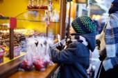 kleiner süßer Junge in der Nähe von Süßwarenstand, der gezuckerte Äpfel und Schokoladenfrüchte kauft. Glückskind auf dem Weihnachtsmarkt in Deutschland. Traditionelle Freizeit für Familien an Weihnachten. Feiertag, Feier, Tradition.
