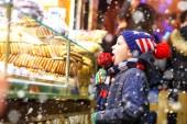 Glückliches Kind isst auf dem Weihnachtsmarkt auf mit rotem Zucker überzogenem Apfel