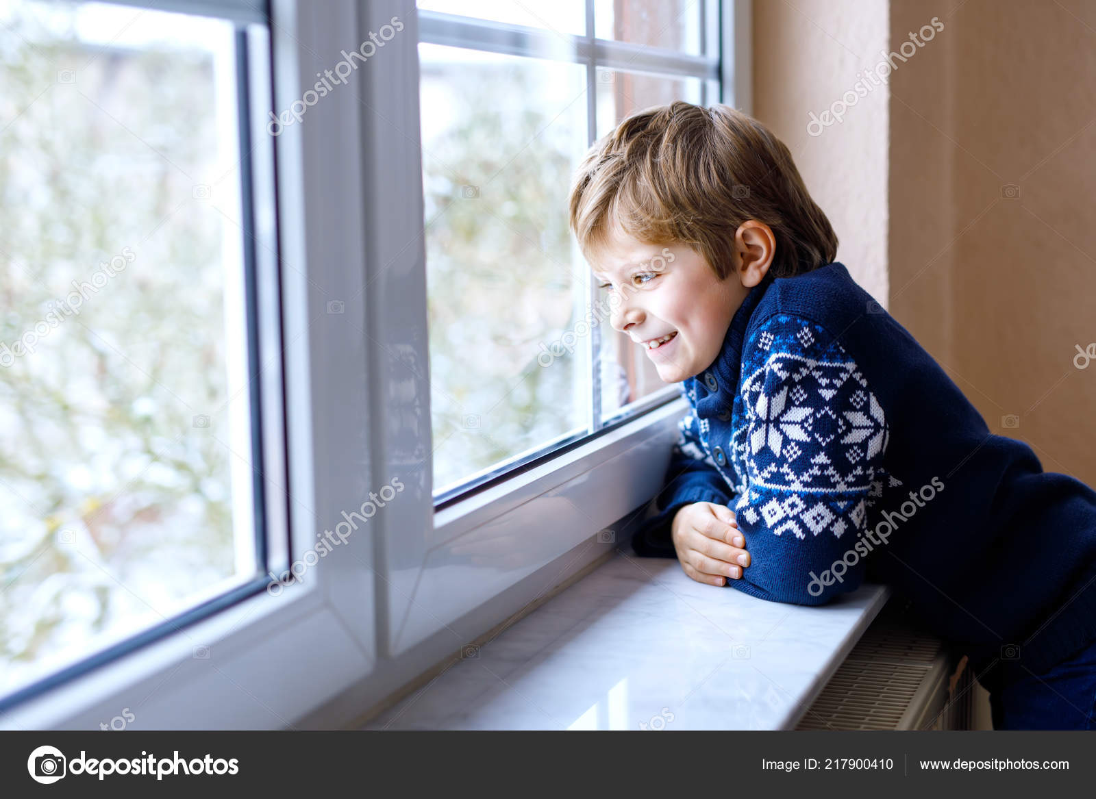 Happy adorable kid boy sitting near window and looking outside on