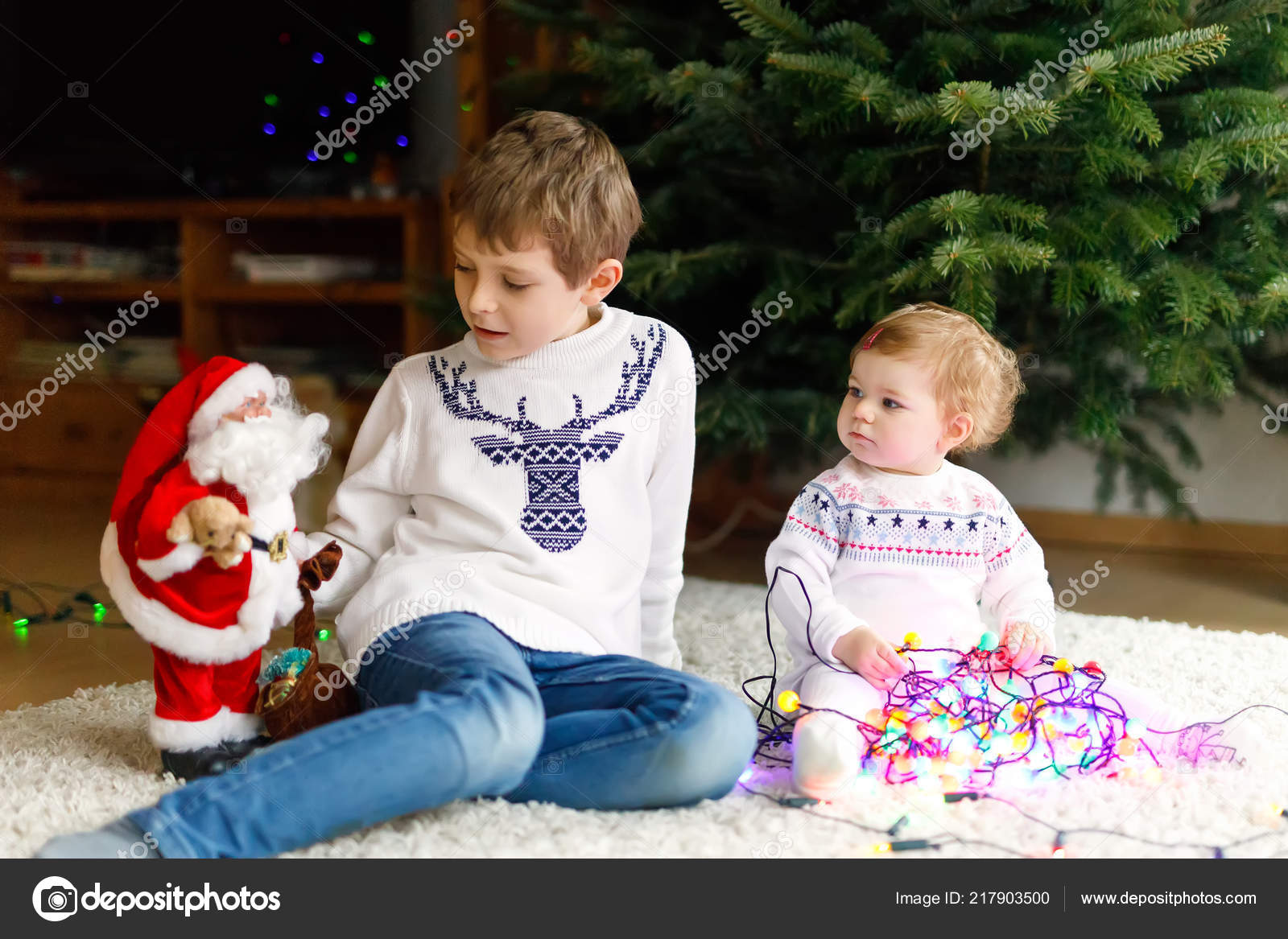 26a760c03 Adorable baby girl and brother holding colorful lights garland and toy  Santa Claus in cute hands. Little children, kid boy and toddler girl in  festive ...