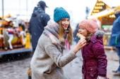 junge Mutter und Tochter essen mit weißer Schokolade überzogene Früchte am Spieß auf dem traditionellen deutschen Weihnachtsmarkt