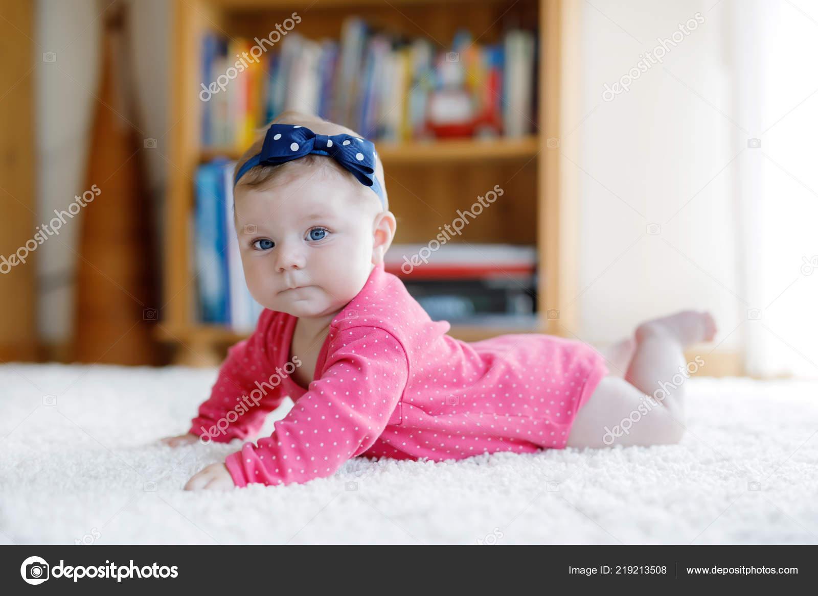 e5095dc417 Neonata con gli occhi azzurri che si trova sulla pancia. Asilo nido per  bambini. Tessile e biancheria da letto per bambini. Ragazza carina felice  del nuovo ...
