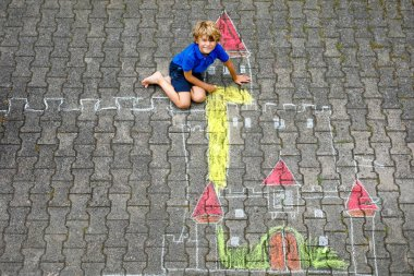 Little kid boy drawing knight castle and fortress with colorful chalks. Happy preschool child having fun with creating chalk picture. Creative leisure for kids and children in summer