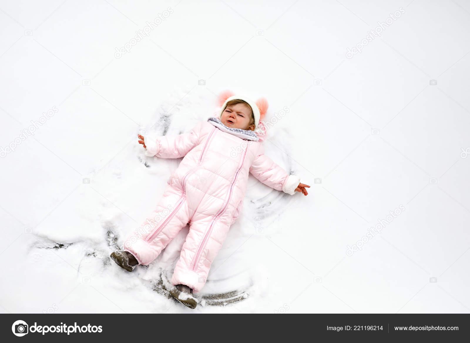 513d36944 Schattig klein babymeisje in kleurrijke winterkleren maken sneeuw ...