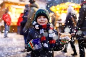 Der kleine süße Junge isst Bratwurst und trinkt auf dem Weihnachtsmarkt heißen Kinderpunsch. Glückskind auf dem traditionellen Familienmarkt in Deutschland, München. Lachender Junge in bunter Winterkleidung