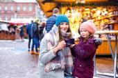 Junge Frau und süßes Mädchen mit einer Tasse dampfender heißer Schokolade oder Kinderpunsch