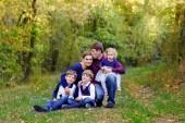 Ritratto di giovani genitori con tre bambini. Madre, padre, due i fratelli ragazzi ragazzi e sorella di piccolo bambino sveglio che ha divertimento insieme nella foresta di autunno. Famiglia di cinque felice