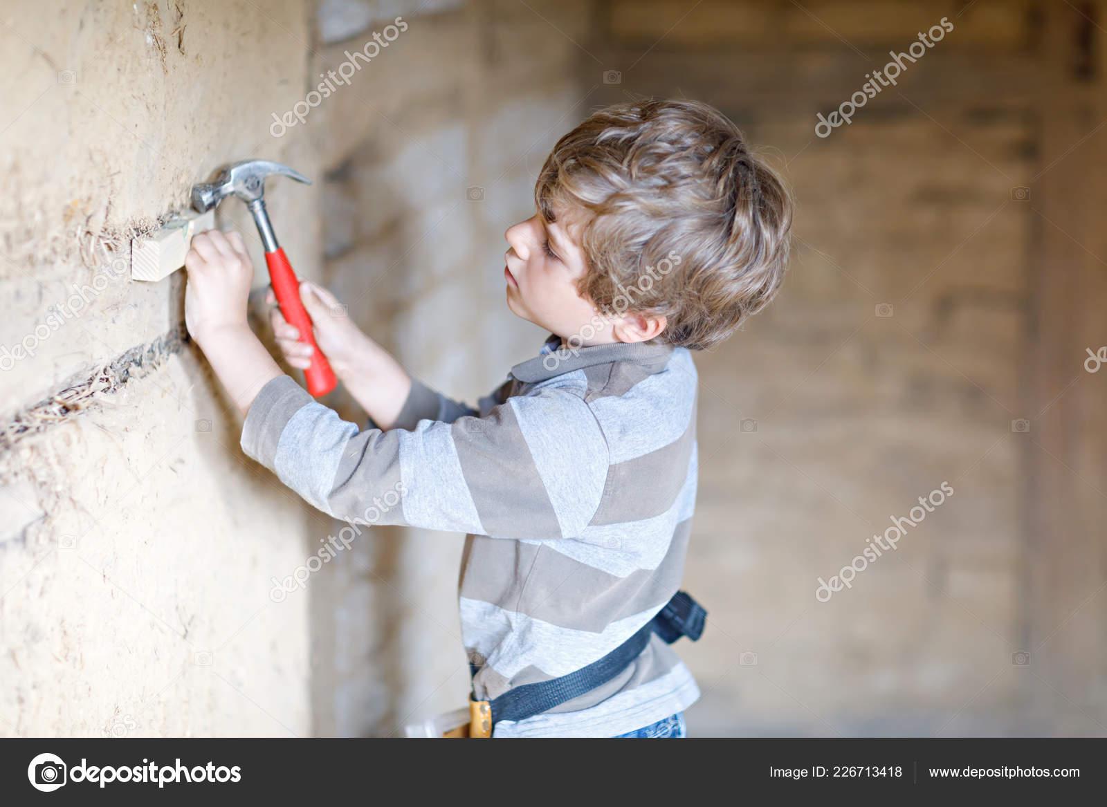 917850957f Garoto menino ajudando com ferramentas de brinquedo no canteiro de obras.  Engraçado criança de 6 anos se divertindo na construção de nova casa da  família.