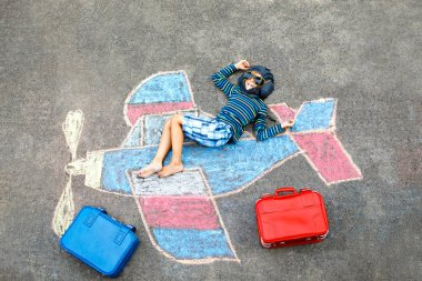 Little kid boy having fun with with airplane picture drawing with colorful chalks on asphalt. Child painting with chalk and crayon and going on vacations or dreaming of pilot profession.