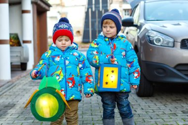 Two little kids boys holding selfmade lanterns for a Halloween or St. Martin procession. Beautiful brothers, cute siblings happy about children and family parade in kindergarten. German tradition