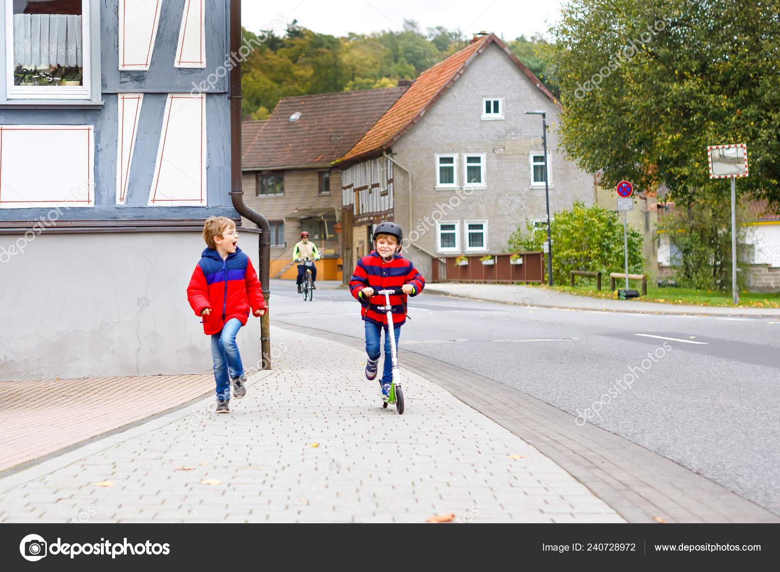 da77e9a9d743a Deux petits écoliers garçons en cours d exécution et conduite sur scooter  journée d automne. Enfants heureux en vêtements colorés et de la  circulation en ...