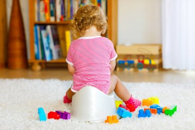 Closeup of cute little 12 months old toddler baby girl child sitting on potty. Kid playing with educational wooden toy. Toilet training concept. Baby learning, development steps