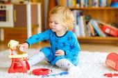 Adorabile bambino bambina sveglia che gioca con la bambola. Bambino bambino sano felice avendo divertimento con il gioco di ruolo, giocando madre a casa o scuola materna. Attiva figlia con il giocattolo.