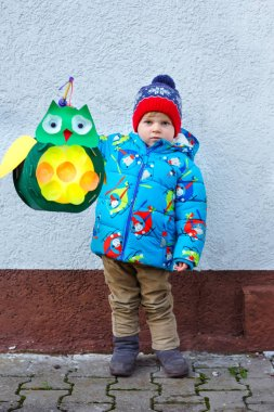 Little kid boy holding selfmade lanterns for a Halloween or St. Martin procession. Beautiful healthy cute child happy about children and family parade in kindergarten. German tradition Martinsumzug